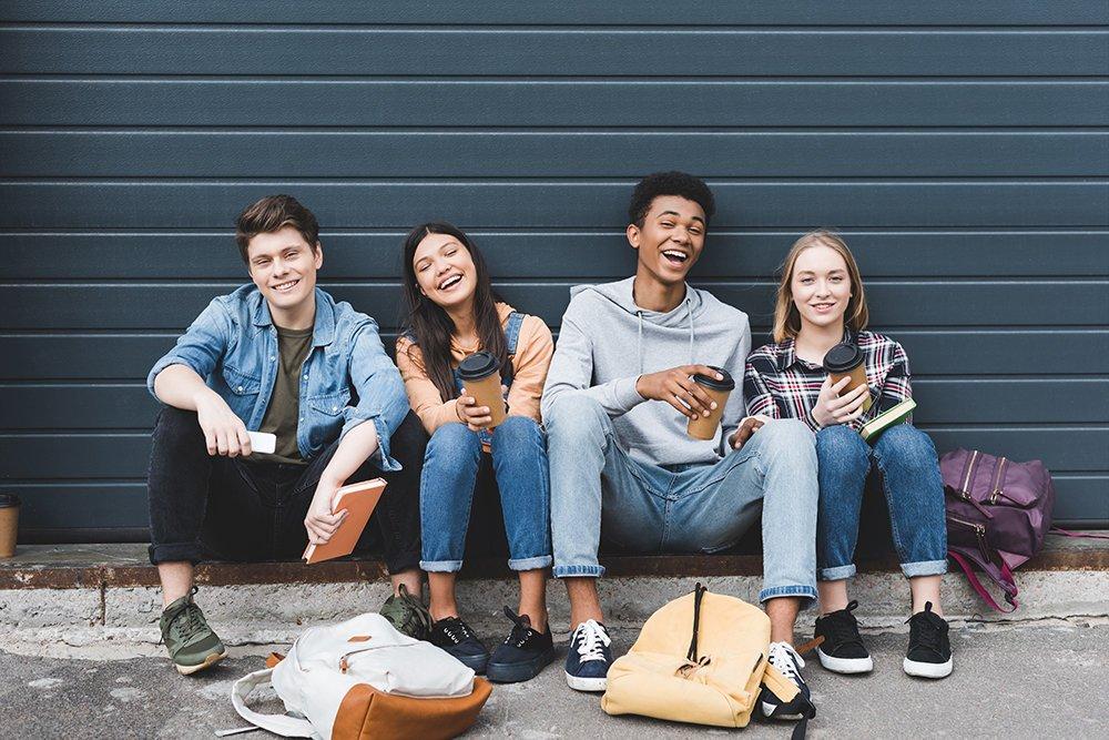Nuoret istuvat rivissä ja katsovat hymyillen kameraan